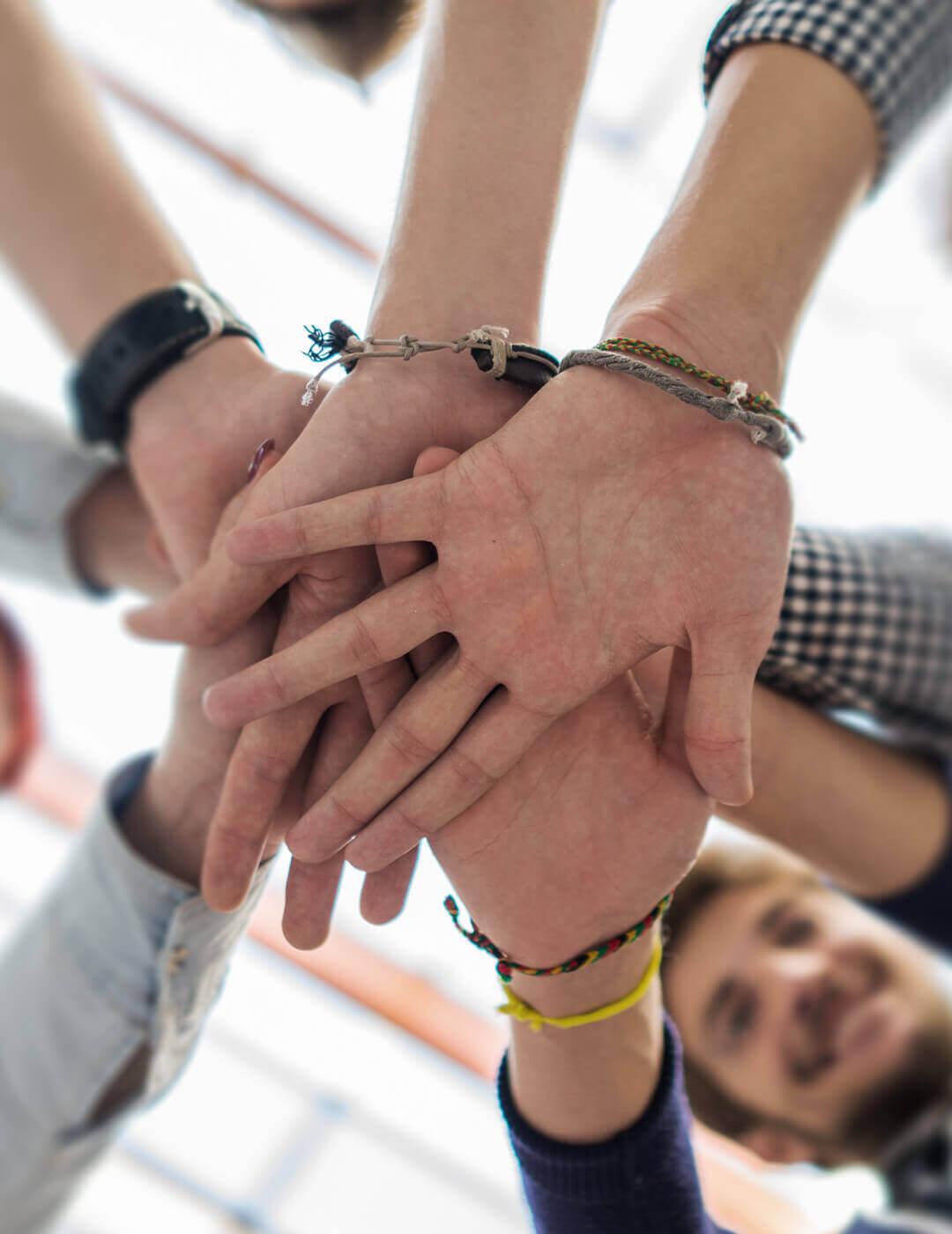 Menschen legen Hände übereinander