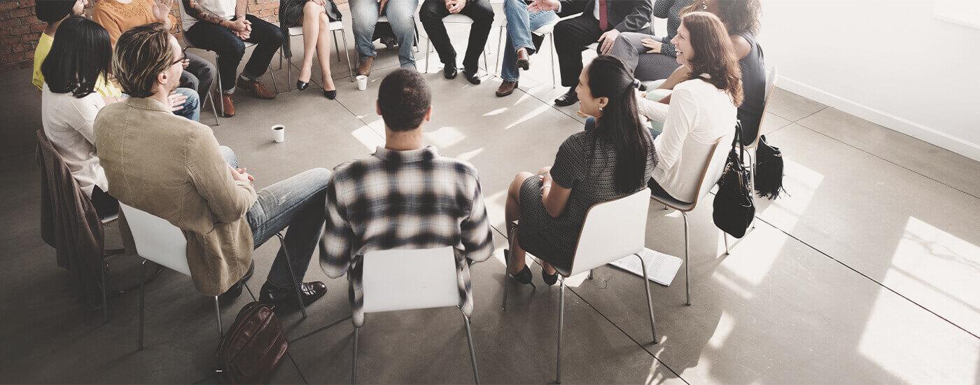 Menschen sitzen im Stuhlkreis